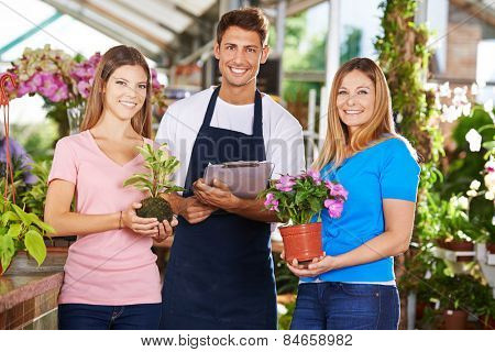 Happy gardener team group in nursery shop with plants and flowers