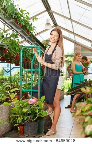Young smiling woman getting apprenticeship in a nursery shop