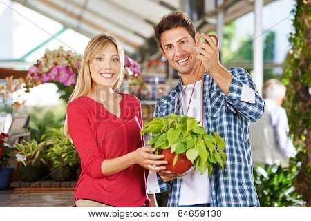 Happy couple with a green philodendron in a nursery shop