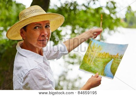 Senior woman painting a watercolor picture in nature in summer