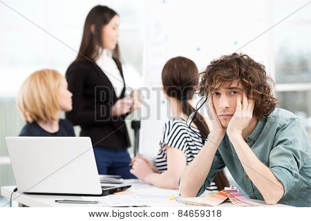 Sad creative businessman looking at camera