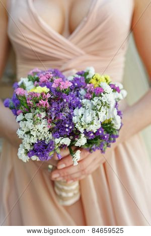 beautiful wedding bouquet of multicoloured statice flowers in hands of the bride