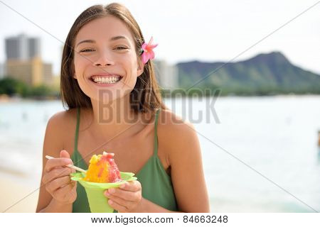 Hawaii woman on Waikiki Beach eating Hawaiian shave ice, a local shaved ice dessert. Happy smiling mixed race Asian Caucasian female model enjoying traditional Hawaiian snack. Oahu, Hawaii, USA.