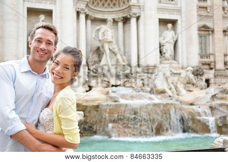 Rome travel - tourist couple on travel by Trevi Fountain in Rome, Italy. Happy young romantic couple traveling in Europe taking self-portrait with smartphone camera. Man and woman happy together
