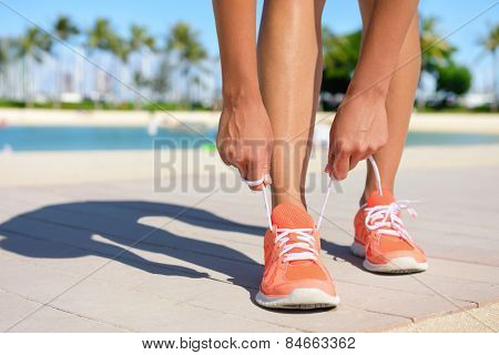 Sport fitness, Exercise running and lifestyle concept. Runner woman lacing running shoes trainers tying laces before jogging on a run. Fit healthy female feet and shoe close up.