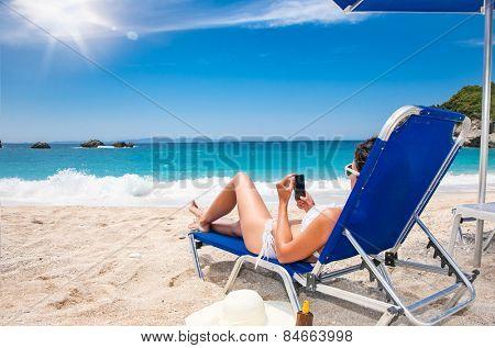 Beautiful woman with phone  in sunhat  enjoying on beach. Greece.