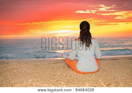 Relaxed sexy young brunette woman sitting on a deserted tropical beach at sunset. Greece.