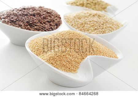 some bowls with amaranth, brown flax, quinoa and buckwheat seeds on a white surface