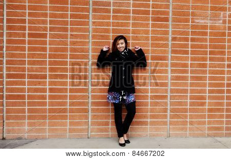 Smiling Attractive Asian American Woman Standing Brick Wall