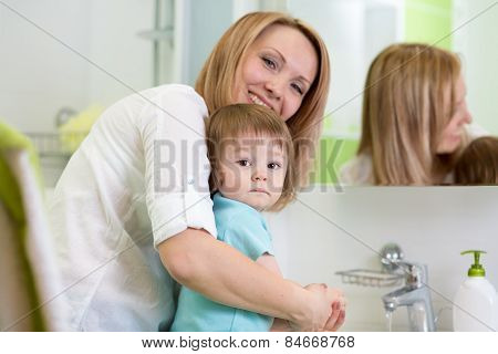 Mother Teaches Kid Washing Hands In Bathroom