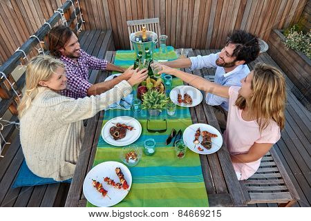 Group of friends toasting to a celebration with drinks while hanging out at a restaurant outdoors