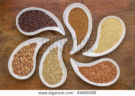 gluten free grain abstract - top view of teardrop shaped bowls with quinoa, teff, millet, rice, sorghum and buckwheat grains against grunge wood