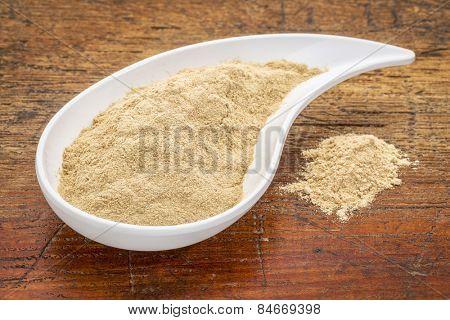 maca root powder in a teardrop shaped bowl against grunge wood
