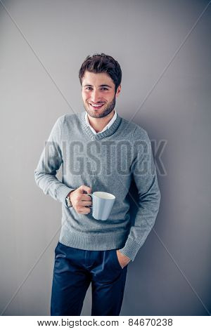 Handsome young smiling businessman with his coffee mug against a grey wall