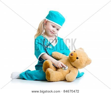 Adorable child with clothes of doctor examining  bear toy
