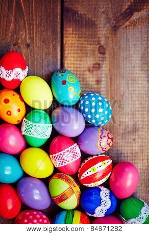 Easter eggs of different colors on wooden background