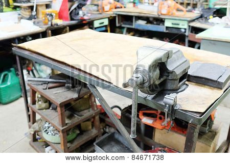 The image of a old vice on a metal workbench
