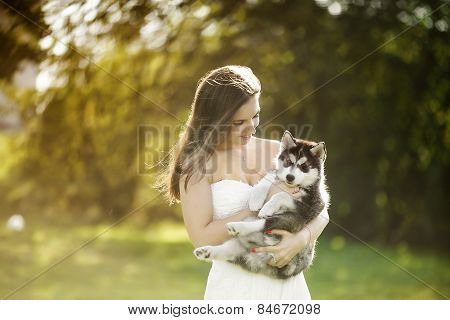 The Girl In The White Dress Hugging A Husky Puppy