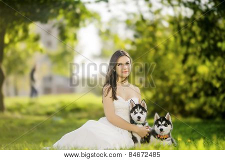 .the Girl In The White Dress Smiles. Sitting On The Grass And Hugging Two Puppies Husky. Summer