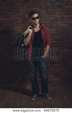 Young hipster man wearing sunglasses casual clothes unbuttoned shirt and denim jeans with bag over s
