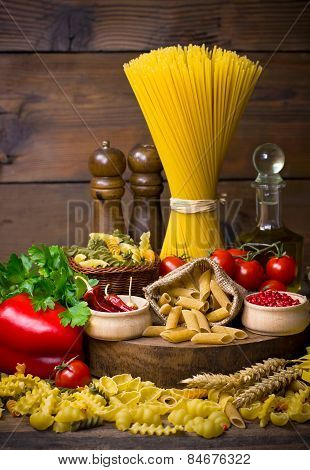 Variety of uncooked pasta and vegetables on the table