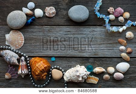 Seashells And Pebbles On The Wooden Table