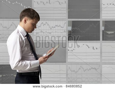 Stock trader looking at tablet computer in office