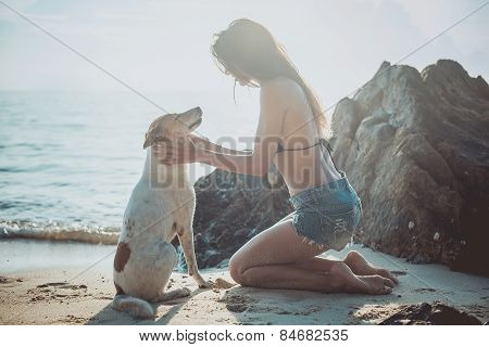 Portrait of beautiful happy young woman sitting playing her pet dog sunset at the beach on sea shore