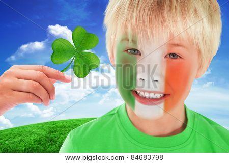 Cute irish boy against green hill under blue sky