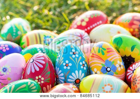 Hand-painted Easter eggs on grass. Floral, colorful spring patterns and designs. Traditional, artistic and unique.