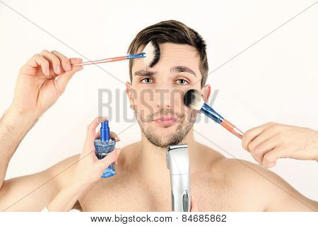 Female hand doing make up young man isolated on white