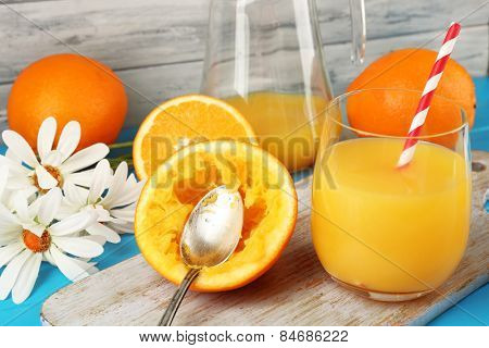 Glass of orange juice with slices, flowers and straws on cutting board on color wooden background