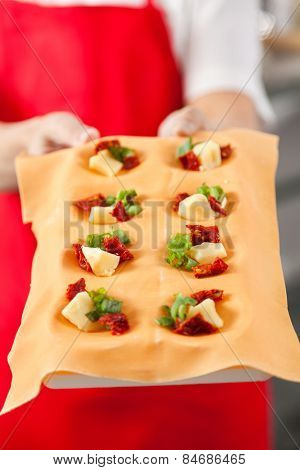 Midsection of female chef holding tray with stuffed ravioli pasta sheet in commercial kitchen