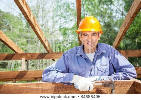 Portrait of smiling male worker holding hammer at construction site