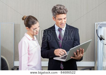 Businessman and female call center employee using laptop in office