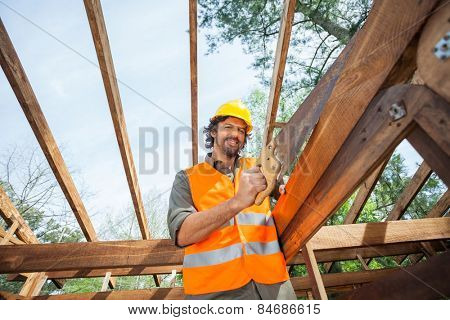 Low angle portrait of male worker cutting wood with handsaw at construction site