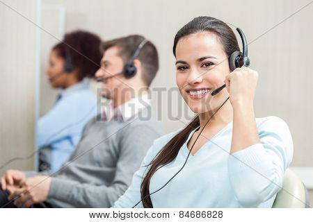 Portrait of smiling female customer service executive with colleagues in background at office