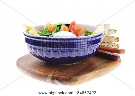 green salad with smoked salmon in bowl on wood