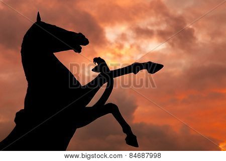 Horse And Snake Monument Silhouette With Over Cloudy Red Sky Background