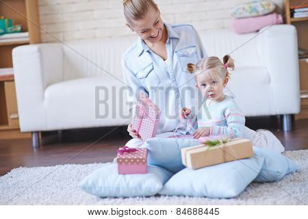 Happy woman looking at her little daughter unpacking giftbox