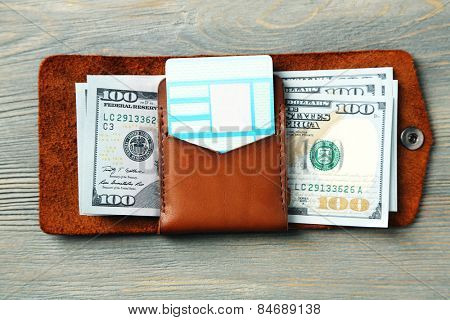 Hand made leather man wallet with money on wooden background