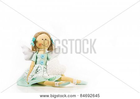 Guardian angel: isolated handmade doll with a white heart in her hands.