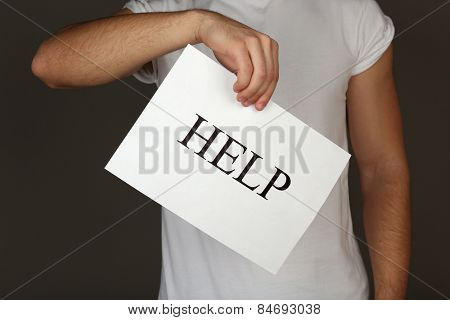 Sheet of paper with Help sign in male hand on dark background