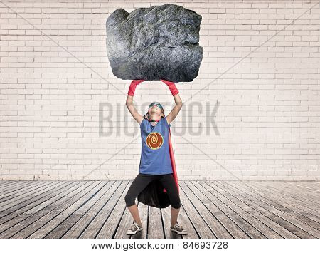 little girl wearing a superhero costume holding a heavy rock