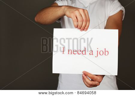 Sheet of paper with inscription I need a job in male hands on dark background