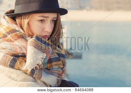retro portret beautiful young sad girl in hat and coat stands on the dock, looking at the blue sea