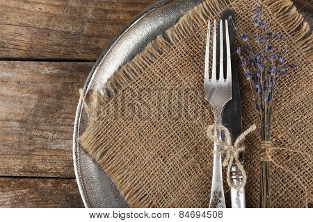 Silverware tied with rope on metal tray with burlap cloth and dried flower on wooden planks background