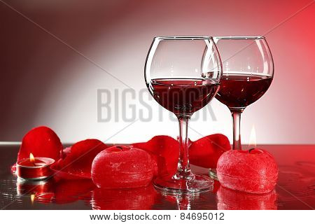Composition with red wine in glasses, red rose petals and decorative heart on colorful background