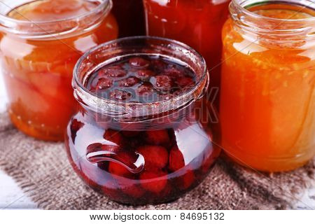 Homemade jars of fruits jam on burlap cloth and color wooden table background