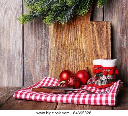 Cutting board with Christmas decoration on wooden planks background